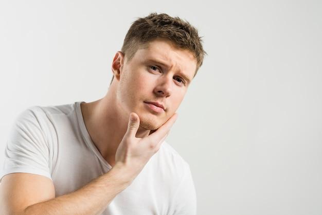 Ritratto di un giovane che tocca il suo viso su sfondo bianco Foto Gratuite