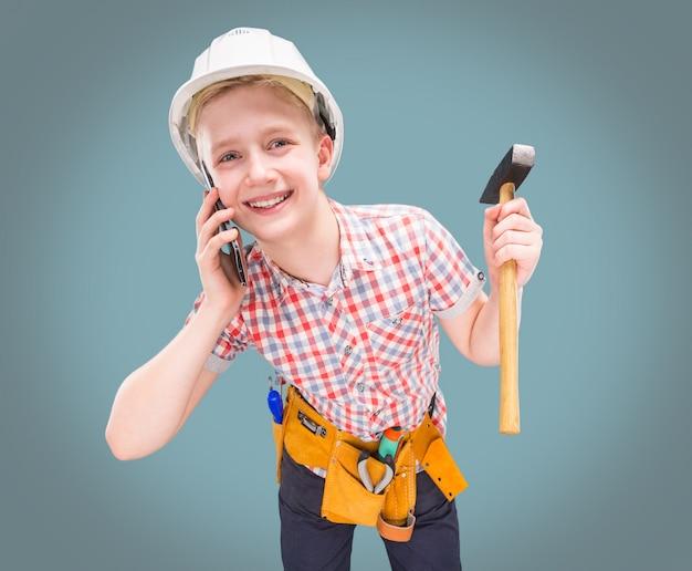Ritratto di un giovane costruttore in un casco e una misura di nastro in mano Foto Premium