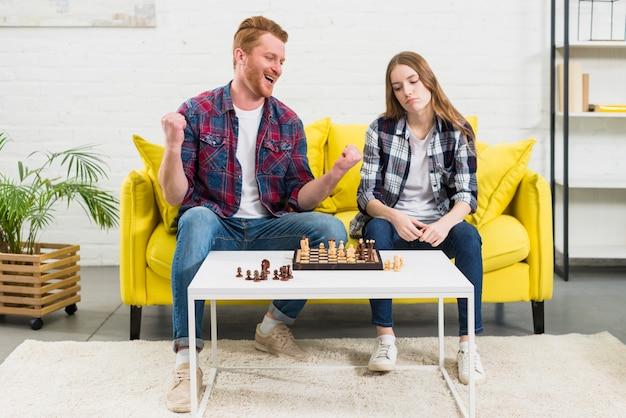 Ritratto di un giovane eccitato seduto con la sua amica triste giocare a scacchi Foto Gratuite