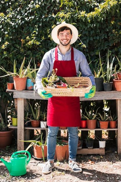 Ritratto di un giovane giardiniere maschio felice che tiene le piante in vaso nel canestro Foto Gratuite