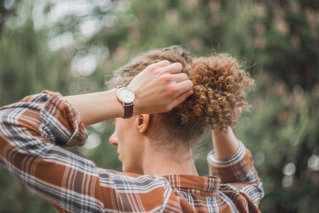Ritratto di un giovane ragazzo dai capelli ricci in un parco estivo Foto Premium