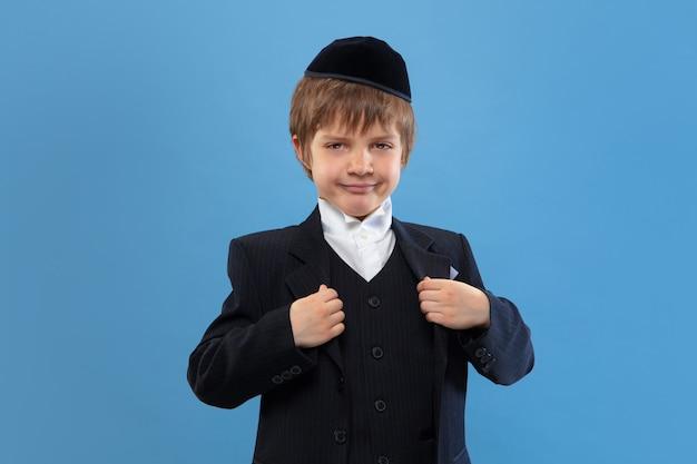 Ritratto di un giovane ragazzo ebreo ortodosso isolato su studio blu Foto Gratuite