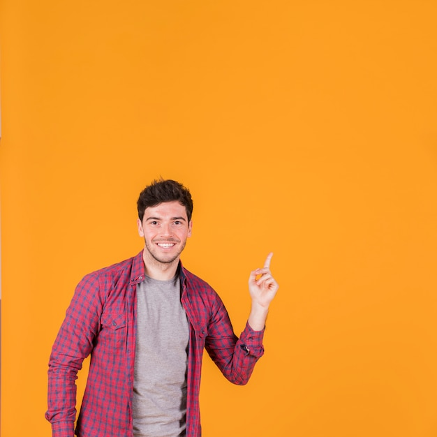 Ritratto di un giovane sorridente che punta il dito verso l'alto contro uno sfondo arancione Foto Gratuite