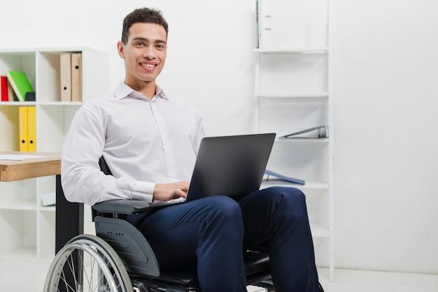 Ritratto di un giovane sorridente che si siede sulla sedia a rotelle con il computer portatile che guarda l'obbiettivo Foto Gratuite