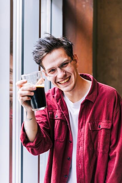 Ritratto di un giovane sorridente, mostrando il bicchiere di birra a porte chiuse Foto Gratuite