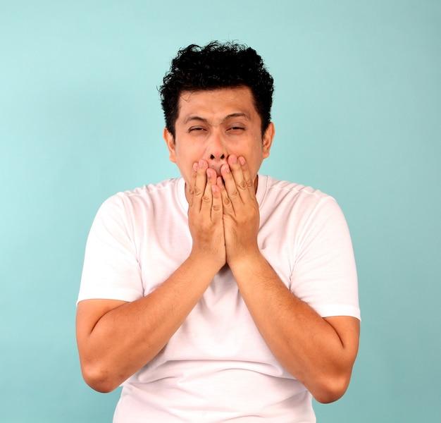 Ritratto di un giovane uomo asiatico deluso, concentrandosi su uomini in magliette bianche su un blu. Foto Premium