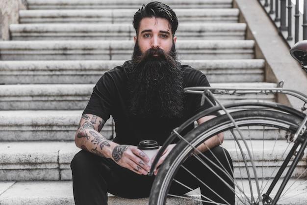 Ritratto di un giovane uomo barba con la sua bicicletta guardando la fotocamera Foto Gratuite
