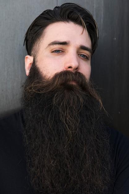 Ritratto di un giovane uomo barbuto contro sfondo grigio Foto Gratuite