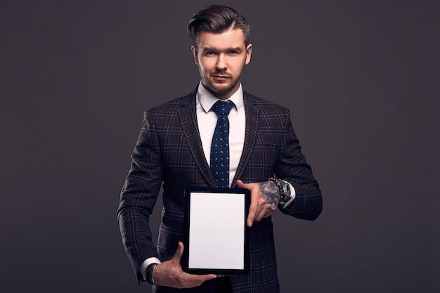 Ritratto di un giovane uomo brutale elegante con tavoletta Foto Premium