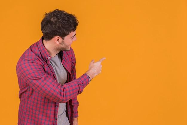 Ritratto di un giovane uomo che punta il dito e guardando sullo sfondo arancione Foto Gratuite