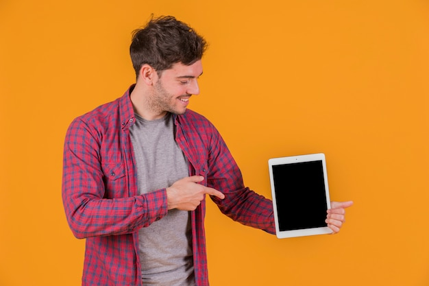 Ritratto di un giovane uomo che punta il dito sulla tavoletta digitale contro uno sfondo arancione Foto Gratuite