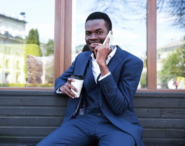 Ritratto di un giovane uomo d'affari africano che parla sul telefono cellulare Foto Gratuite