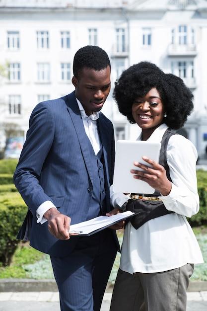 Ritratto di un giovane uomo d'affari africano e imprenditrice guardando tavoletta digitale Foto Gratuite