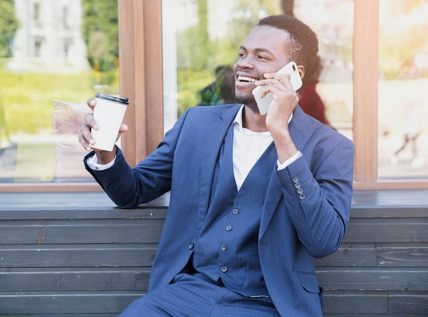 Ritratto di un giovane uomo d'affari africano tenendo la tazza di caffè da asporto a parlare sul telefono cellulare Foto Gratuite