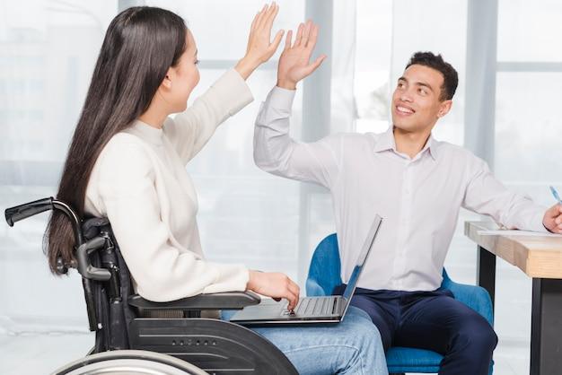 Ritratto di un giovane uomo d'affari sorridente che dà livello cinque alla giovane donna che si siede sulla sedia a rotelle con il computer portatile Foto Gratuite