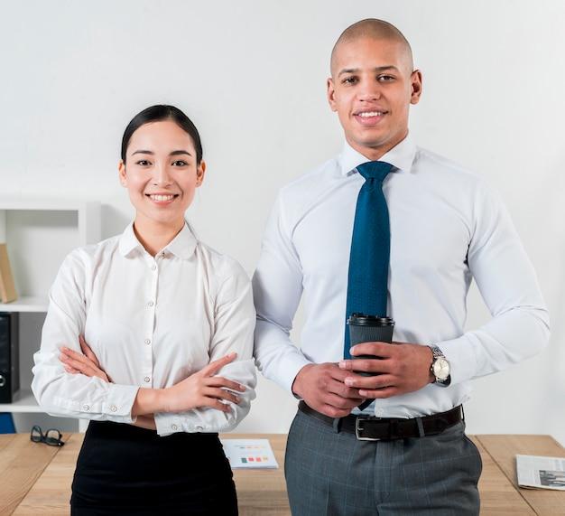 Ritratto di un giovane uomo d'affari sorridente che tiene la tazza di caffè eliminabile disponibila che sta con la donna di affari Foto Gratuite
