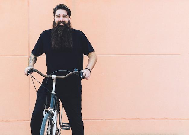Ritratto di un giovane uomo in sella alla bicicletta su sfondo beige Foto Gratuite