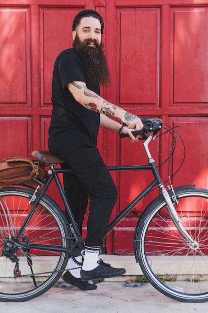 Ritratto di un giovane uomo seduto sulla bicicletta contro la porta rossa Foto Gratuite
