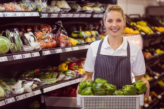 Ritratto di un lavoratore biondo sorridente che tiene verdure Foto Premium
