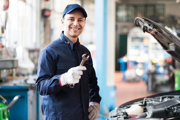 Ritratto di un meccanico sorridente che tiene una chiave nel suo garage Foto Premium