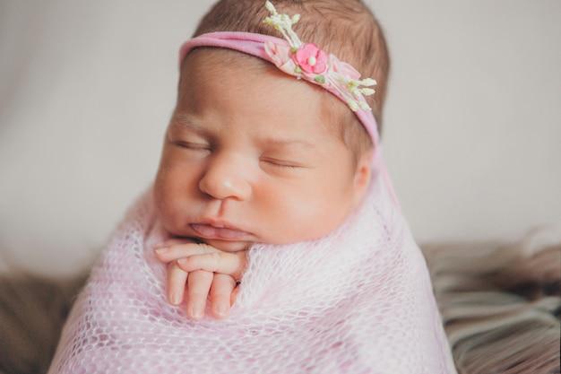 Ritratto di un neonato che dorme in una fascia con fiore. concetto di salute: fecondazione in vitro, accessori per bambini Foto Premium