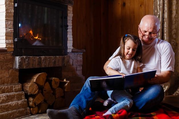 Ritratto di un nonno che indossa una maglietta bianca che legge una storia alla sua piccola e graziosa nipotina Foto Premium