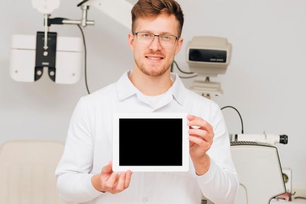 Ritratto di un optometrista maschio che presenta il modello di tablet Foto Gratuite
