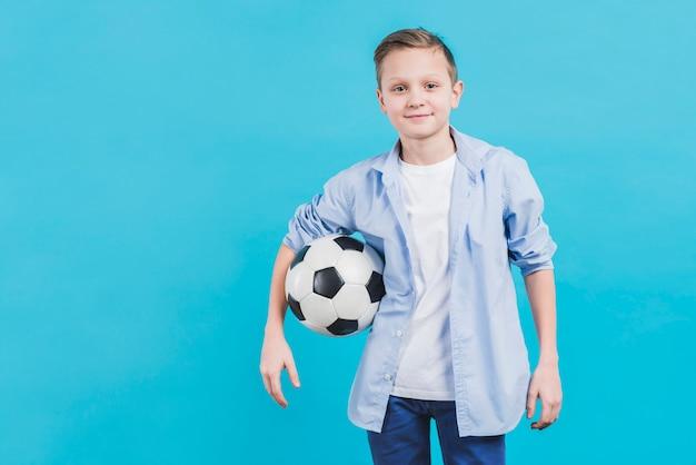 Ritratto di un pallone da calcio della tenuta del ragazzo che guarda alla macchina fotografica che sta contro il cielo blu Foto Gratuite