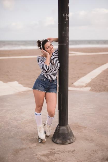 Ritratto di un pattinatore femmina sorridente in piedi vicino al pilastro di ferro Foto Gratuite