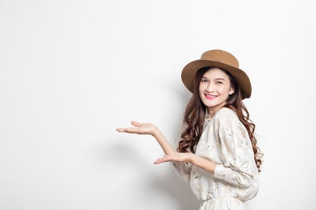 Ritratto di un presentatore asiatico sorridente della donna su fondo bianco, donna asiatica che indica lo spazio della copia, bella ragazza tailandese. Foto Premium