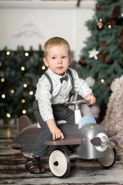 Ritratto di un ragazzino seduto su un aeroplanino giocattolo vintage vicino a un albero di natale. decorazioni natalizie. il ragazzo si rallegra del suo regalo di natale. buon natale e felice anno nuovo Foto Premium