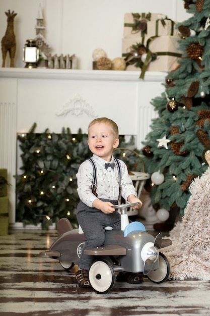 Ritratto di un ragazzino seduto su un aeroplanino giocattolo vintage vicino a un albero di natale Foto Premium