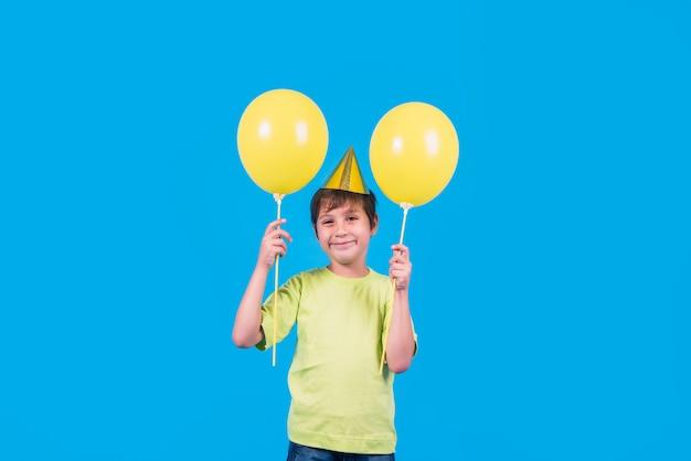 Ritratto di un ragazzino sveglio che tiene i palloni gialli contro il contesto blu Foto Gratuite