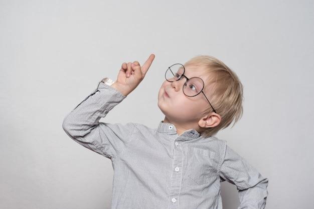 Ritratto di un ragazzo biondo carino con grandi occhiali. dito rivolto verso l'alto. Foto Premium