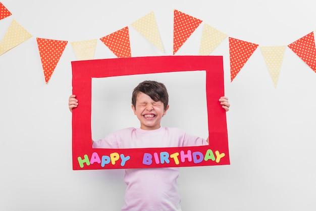 Ritratto di un ragazzo carino tenendo la cornice di compleanno con gli occhi chiusi Foto Gratuite