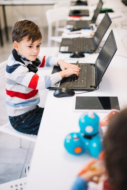 Ritratto di un ragazzo con laptop guardando bambino che gioca con il giocattolo in classe Foto Gratuite