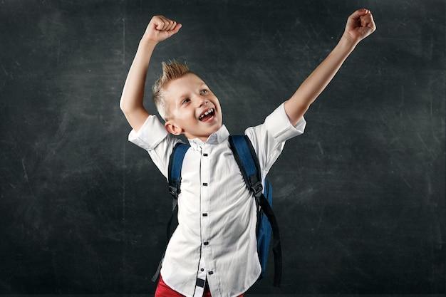 Ritratto di un ragazzo di una scuola elementare su uno sfondo di un consiglio scolastico Foto Premium