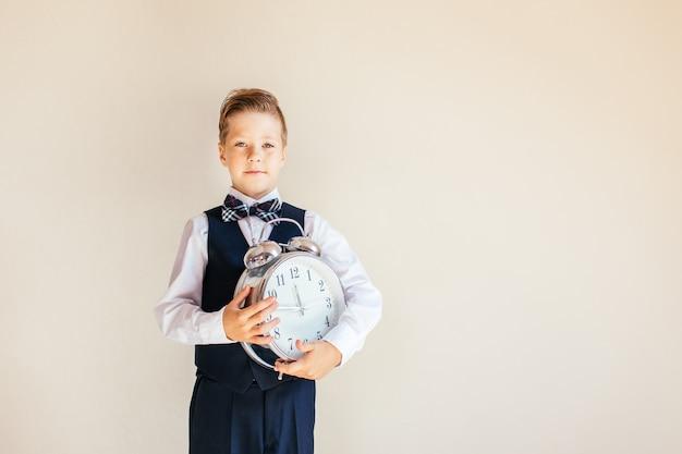 Ritratto di un ragazzo in abito grigio con grande orologio. ragazzo carino tenendo grande orologio. bambino torna a scuola, su sfondo neutro. concetto di educazione e tempo. Foto Premium