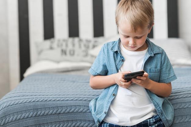 Ritratto di un ragazzo in piedi davanti al letto con il cellulare Foto Gratuite