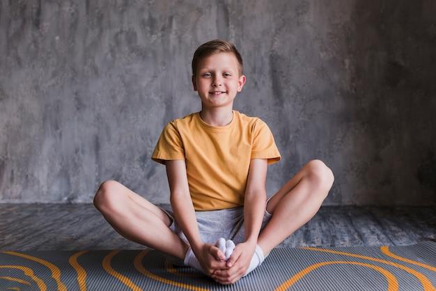 Ritratto di un ragazzo sorridente che si siede sulla stuoia di esercizio che guarda l'obbiettivo Foto Gratuite