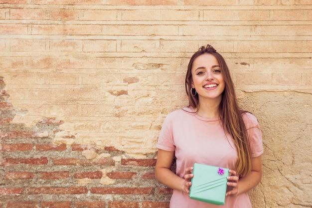 Ritratto di un regalo sorridente della tenuta della giovane donna davanti alla vecchia parete Foto Gratuite