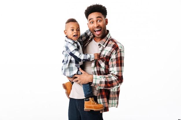 Ritratto di un uomo africano felice che tiene il suo piccolo figlio Foto Gratuite