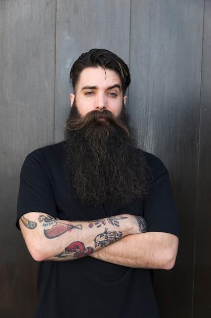 Ritratto di un uomo barbuto che attraversa le sue braccia contro il muro nero Foto Gratuite