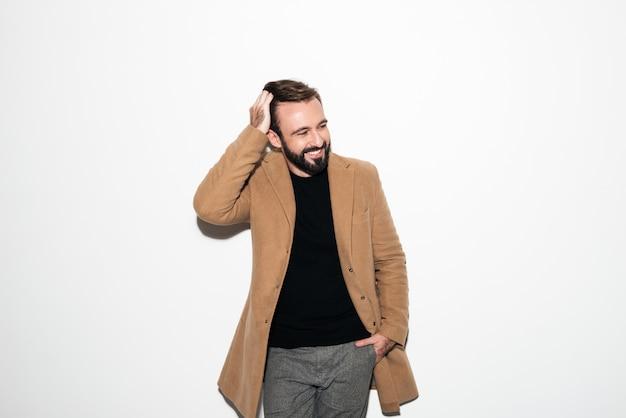 Ritratto di un uomo barbuto vestito con un cappotto ridendo Foto Gratuite