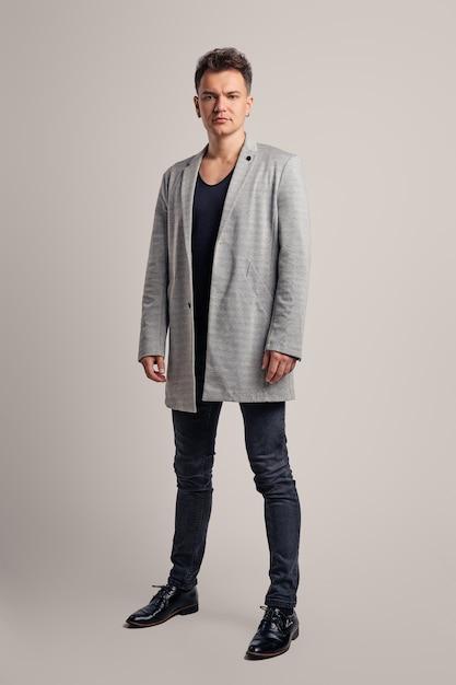 Ritratto di un uomo bello che indossa giacca di lana, camicia nera e jeans Foto Premium