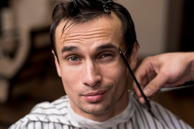 Ritratto di un uomo che ottiene un taglio di capelli Foto Gratuite