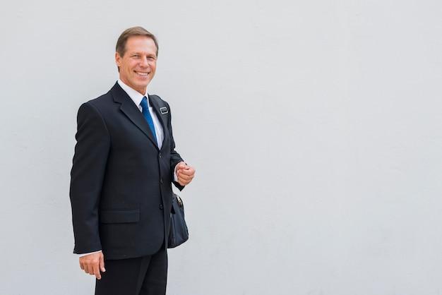 Ritratto di un uomo d'affari felice in piedi contro il contesto grigio Foto Gratuite