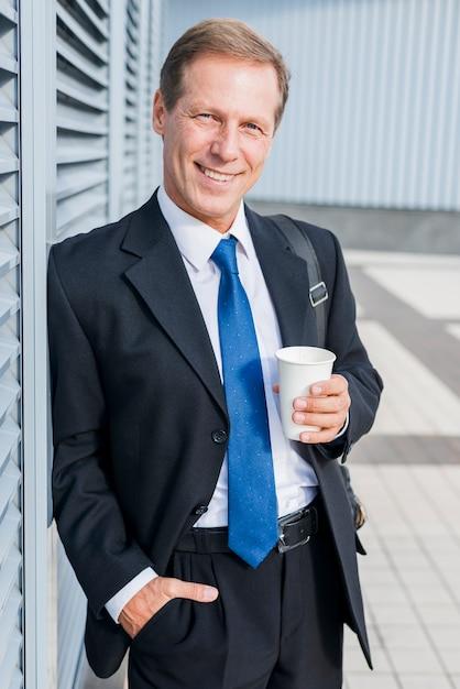 Ritratto di un uomo d'affari maturo felice con una tazza di caffè Foto Gratuite