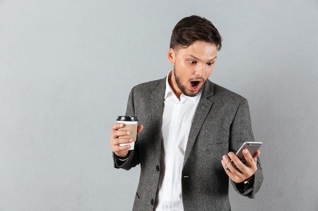 Ritratto di un uomo d'affari scioccato guardando il telefono cellulare Foto Gratuite