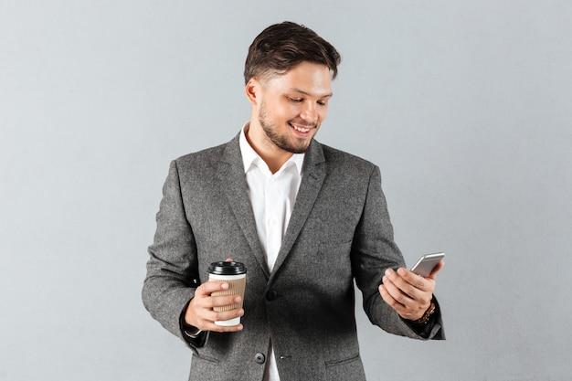 Ritratto di un uomo d'affari sorridente guardando il cellulare Foto Gratuite